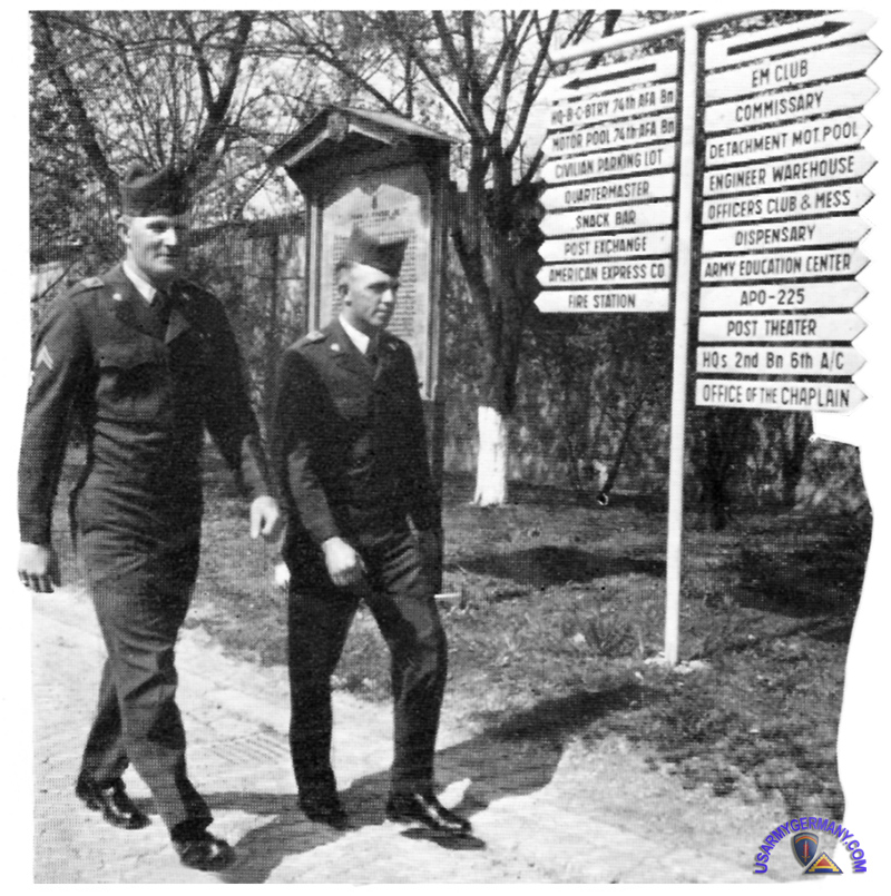 soldiers at Pinder Kaserne walk past the directional signs (at the